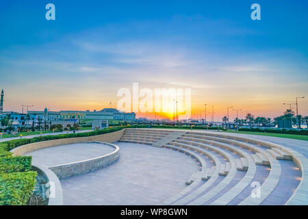 Outdoor event seating in park under sunset glow near The Corniche in old city of Doha at dusk, Qatar. - Stock Photo