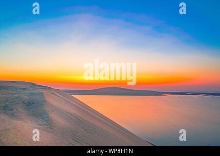 Desert at sunrise amazing sky and water colors before the sun rises above the horizon in Sealine Desert, Doha, Qatar.