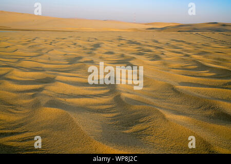 Desert at sunrise light and shade from low angle of sun on surface wind ripples on sand  for backgrounds.