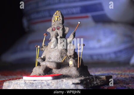 Lord Ganesha in selective focus, made of clay with colorful blur background, in indian village - Stock Photo
