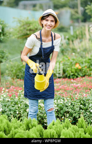 Pretty smiling gardening specialist spraying plants in nursery garden to protect them from fungal disease - Stock Photo