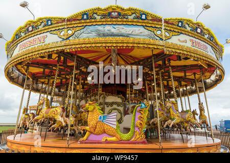 Brightly coloured carousel on beach promenade in Morecambe, UK. - Stock Photo
