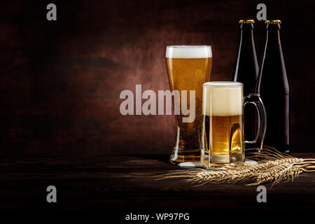 Bottle and two glasses of cold golden beer and wheat spikelets on dark background. copy space - Stock Photo