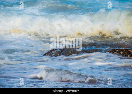 Strong afternoon tide, incoming tide with waves crashing on the rocks on the rocks with strong foamy waves, a backwash, a side wash. Real angry waves. - Stock Photo