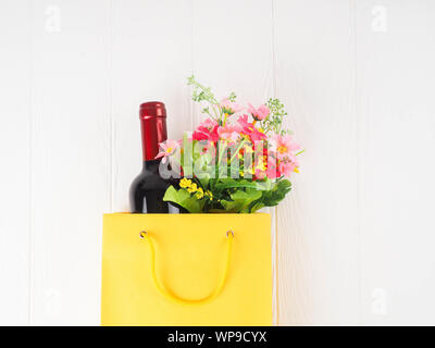 bottle of wine in the package with a gift, flowers, on wooden background, copy space, gift, holiday, Dating, flat lay