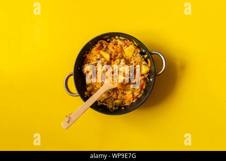 top view of vegetable stew mix in cauldron on a color surface with wooden stick - Stock Photo