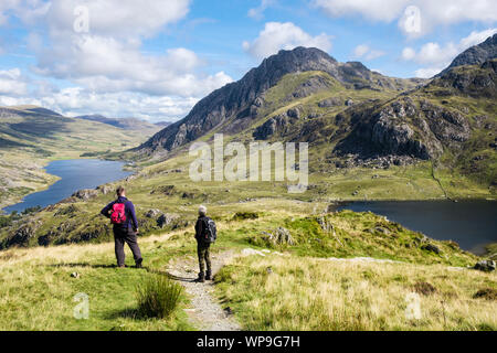 Two hikers hiking on path from Y Garn above Llyn Idwal look at view to Mt Tryfan and Ogwen Valley in Snowdonia National Park. Ogwen Gwynedd Wales UK