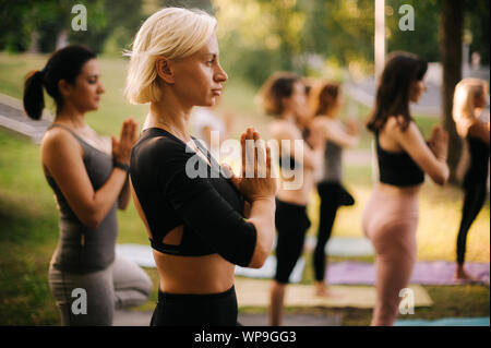 Group of young women are standing in tree pose or Vrikshasana in city park - Stock Photo