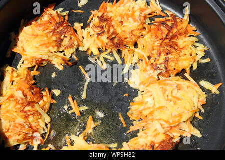 delicious potato pancakes are fried in a pan - Stock Photo