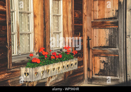 Wooden Alpine chalet with typical red geranium flowers in the windows. Alpine hut. Bavarian wooden huts. Flower decoration. Traditional flower, style. Bavaria, Austria, Switzerland. The Alps. - Stock Photo