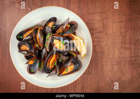 Marinara mussels, moules mariniere, shot from the top on a dark rustic wooden table with a place for text - Stock Photo