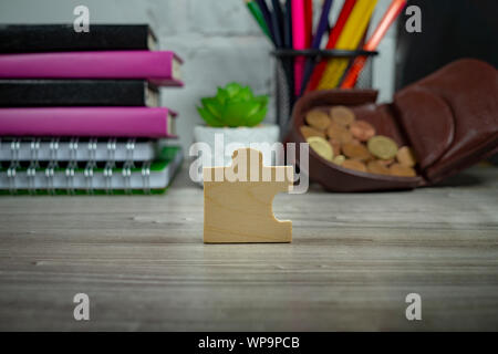 Wooden puzzle piece standing on end on a table with blurred background of school supplies and open purse. Back to school and supplies expenses - Stock Photo