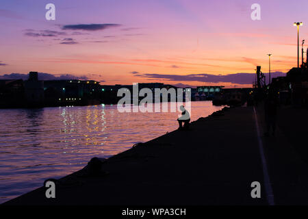 Poole, Dorset, UK, 7th September 2019, Weather: Sitting on the dock of the bay. A man sits and takes in the scene as a glorious orange and purple sunset descends over the harbour and quayside. The reflection in the water intensifies the colourful but relaxed evening mood. Credit: Paul Biggins/Alamy Live News - Stock Photo