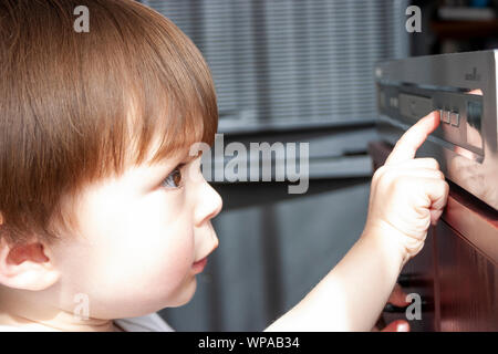 Caucasian child, 3-4 year old Close up of boy's face looking closely at DVD player in front of him, and pressing the play button with one finger. - Stock Photo