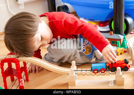 Caucasian child, 3-4 year old, indoors. Floor level view of young boy playing with Thomas Tank engine train set. Pushing train along the track. - Stock Photo