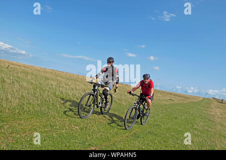 Two cyclists riding bikes on a trail up a hill on the South Downs Way in East Sussex, England UK  KATHY DEWITT - Stock Photo