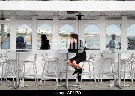 Young man sitting alone at a table on a rainy day on Brighton Pier in East Sussex England UK  KATHY DEWITT - Stock Photo