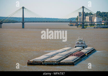 Barge traffic on the Mississippi River at the New Mississippi River Bridge August 28, 2019 in St Louis, Missouri, USA. A typical barge carries 1500 tons of cargo, which is 15 times greater than a rail car and 60 times greater than one trailer truck. An average river tow on the Mississippi River is 15 barges consisting of 5 barges tied together and moving 3 abreast. The same load would require a train 3 miles long or line of trucks stretching more than 35 miles. - Stock Photo