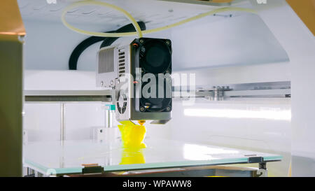 Automatic 3D printer machine working at modern technology exhibition - Stock Photo