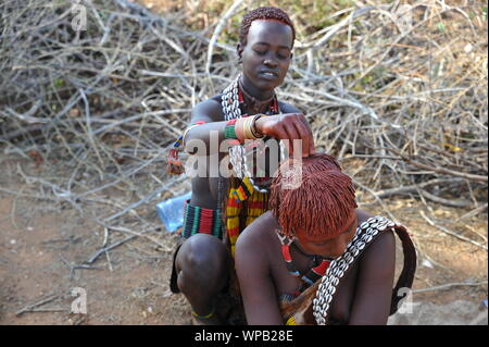 Making the typical red hair red of the Hamer tribe in the south of Ethiopia - Stock Photo