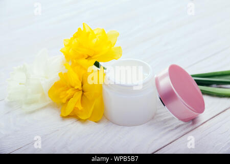 Jar of natural facial cream with flowers on white wooden background. Organic cosmetics. Body care - Stock Photo