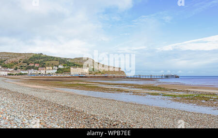 A view of Llandudno's curving shoreline and pier. The Great Orme headland is in the distance and a blue sky is above. - Stock Photo