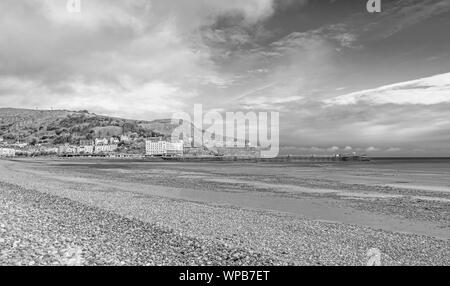 A view of Llandudno's curving shoreline and pier. The Great Orme headland is in the distance and a cloudy sky is above. - Stock Photo