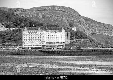 A view of Llandudno's pier and a hotel at dawn.. The Great Orme headland is behind. - Stock Photo