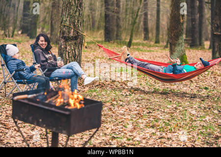 family resting at picnic. fire in grill. laying in hammock sitting in chairs - Stock Photo