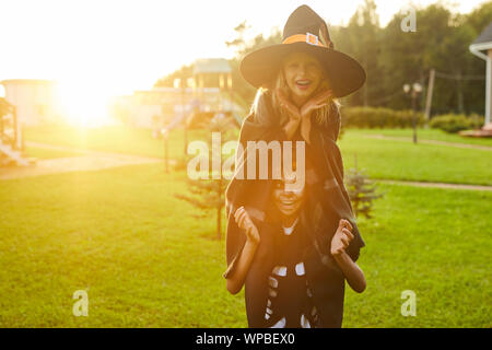 Portrait of two playful little kids, boy and girl, having fun outdoors on Halloween and making faces looking at camera, both wearing costumes, copy space - Stock Photo