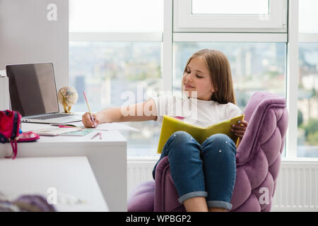 Girl make school homework with pencil and book. School supplies and laptop in background. - Stock Photo