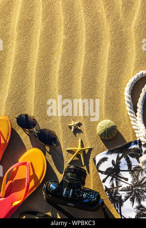 Beach accessories on sand with copy space, top view. Layout on the theme of rest - Stock Photo