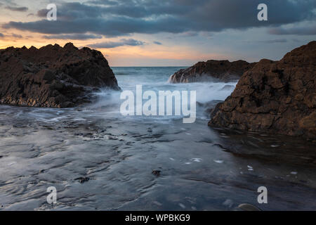 Waves crash over rocks at Westward Ho! beach in North Devon, UK - Stock Photo