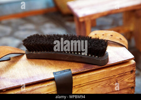 Shoe brush on wooden table. Footwear care item . Large black Horse Hair Shoe Brush and polishing shoes on a wooden table . - Stock Photo