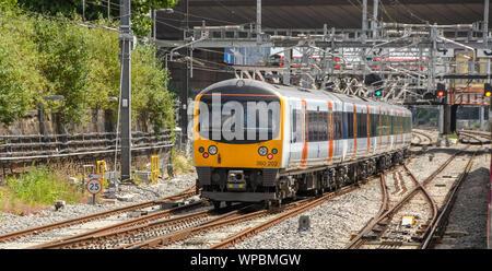 LONDON, ENGLAND - JUNE 2018: Electric powered commuter train on the outskirts of London heading towards Paddington Station - Stock Photo