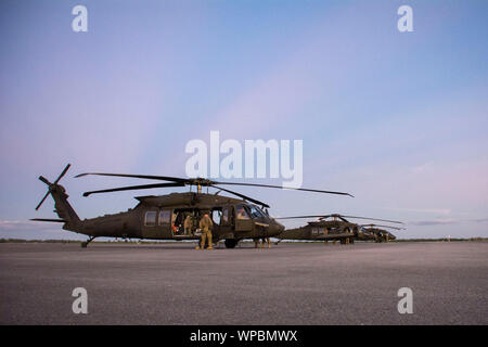 In support of Foreign Disaster Relief efforts in the Bahamas, U.S. Army UH-60 Black Hawk helicopters land at Homestead Air Reserve Base, Florida, Sept. 5, 2019. The Secretary of Defense authorized U.S. Northern Command to provide transportation logistics for the movement of USAID and third party humanitarian commodities and personnel throughout the region and to conduct assessments of critical transportation nodes to facilitate the delivery of humanitarian assistance and maximize the flow of disaster relief into the area. (U.S. Air Force photo by Technical Sgt. Paul Cook) - Stock Photo