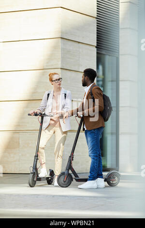 Full length portrait of modern young couple riding electric scooters in city street and chatting, copy space - Stock Photo