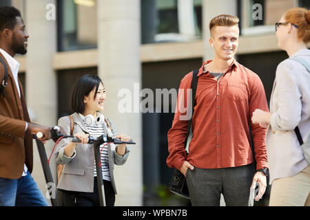 Group of contemporary young people chatting in city street, focus on handsome young man talking to friends outdoors, copy space - Stock Photo