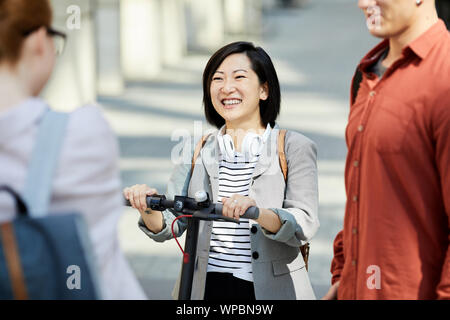 Group of contemporary young people chatting in city street, focus on Asian woman smiling happily, copy space