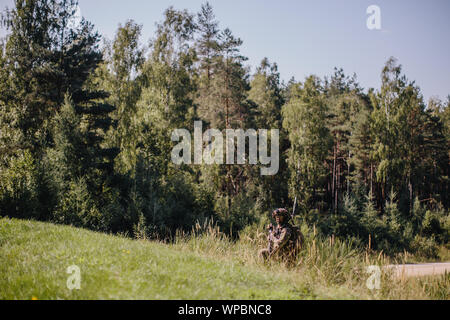 U.S. Army paratrooper assigned to 1st Squadron, 91st Cavalry Regiment, 173rd Airborne Brigade screens his lane for enemy movement during a company-level combined arms live-fire exercise in Grafenwoehr Training Area, Germany, August 23, 2019.     The 173rd Airborne Brigade is the U.S. Army's Contingency Response Force in Europe, providing rapidly deployable forces to Europe, Africa and Central Commands areas of responsibilities. Forward deployed across Italy and Germany, the brigade routinely trains alongside NATO allies to build partnerships and strengthen the alliance. - Stock Photo
