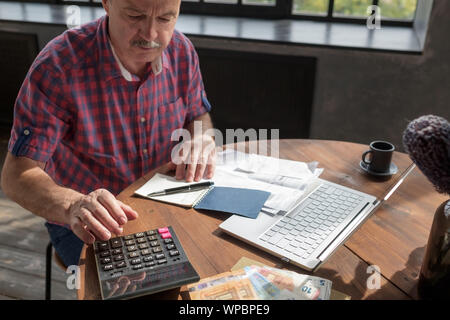 Senior hispanic man busy doing calculation, counting money and bills at home. He is looking through his taxes. - Stock Photo