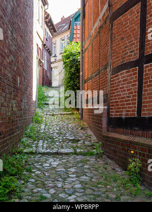Stade, Germany - August 25, 2019: View at cobbled alley in famous historical center  in town of Stade, Germany. A big tourist attraction. - Stock Photo