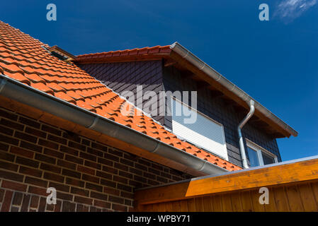 Dormer window with blinds, ceramic tiles visible, against the blue sky. - Stock Photo