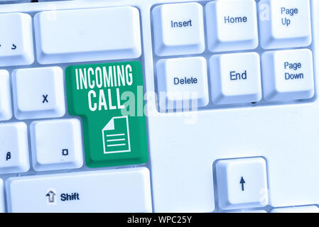 Conceptual hand writing showing Incoming Call. Concept meaning Inbound Received Caller ID Telephone Voicemail Vidcall White pc keyboard with note pape - Stock Photo