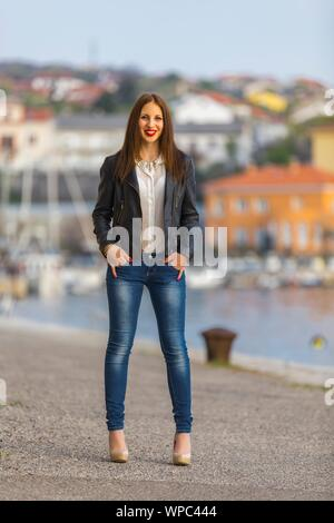 Teen girl in denim pants Beige high-heels standing on seaside hands fingers in pockets looking at camera eye eyes-contact eyeshot smiling Red-lips - Stock Photo