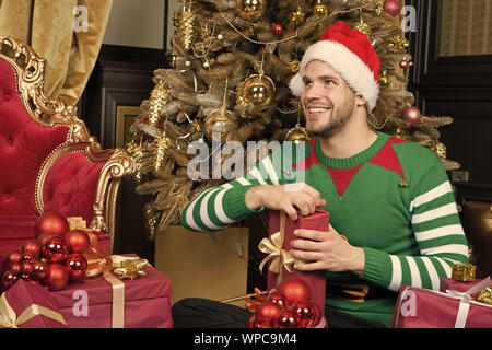 Opening Christmas present. Guy is celebrating Christmas at home. Man in santa hat hold Christmas presents. Happy man with xmas gift boxes. Delivery Christmas gifts. Indulge yourself in joy. - Stock Photo