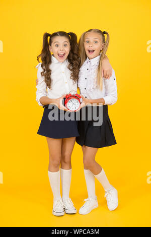 Getting back to class in time. Happy little girls back to school on september 1. Small schoolchildren smiling with clock. Welcome back. Starting a new grade. Back to school is a new step to future. - Stock Photo