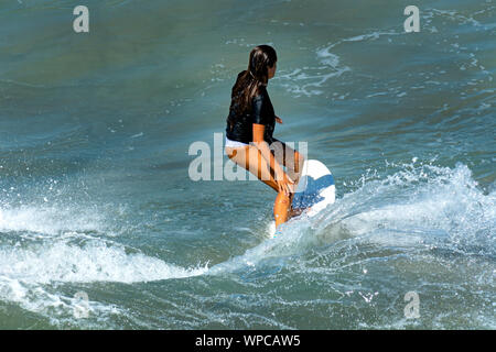 Huntington Beach, Calif. / USA - Sept 7, 2019: Closeup of a tan young woman surfing near the pier on a hot summer afternoon. - Stock Photo