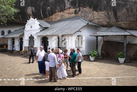 DAMBULLA / SRI LANKA - AUGUST 07, 2019:  The Unspecific people is travelling around of cave in Dambulla, Sri Lanka. The largest cave for the buddha te - Stock Photo
