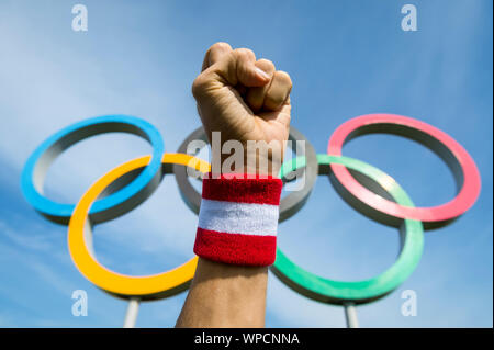 RIO DE JANEIRO - MARCH 15, 2016: A hand wearing red and white Team Japan wristband punches the air in front of Olympic Rings. - Stock Photo